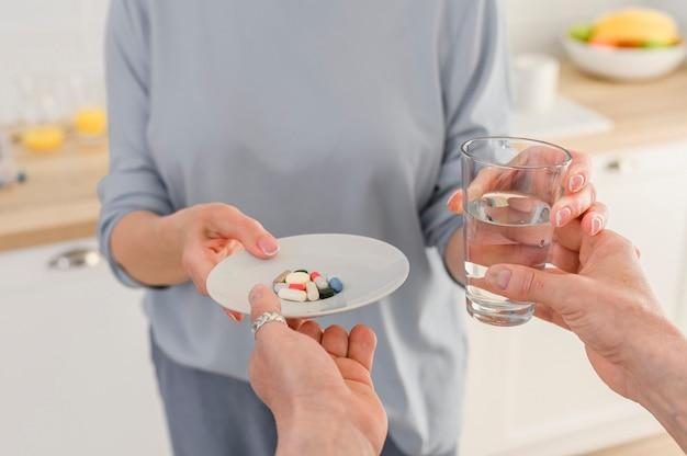 Feche as mãos femininas sênior segurando um copo de água e tomando um conjunto de vitaminas e comprimidos de suplemento