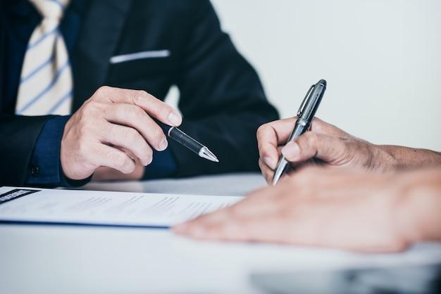 Feche as mãos humanas, apontando para o documento de negócios em reunião no escritório.