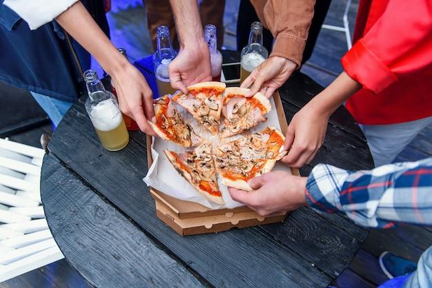 Feche as mãos humanas tomando fatias de pizza italiana saborosa quente da caixa de papelão na festa.