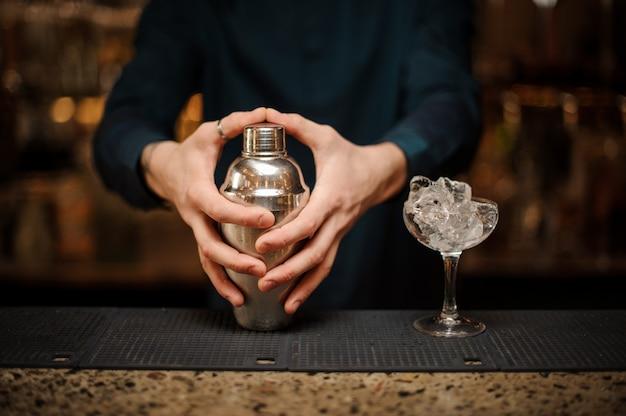 Feche as mãos jovens barmans com agitador