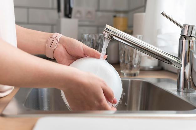 Feche as mãos lavando o prato