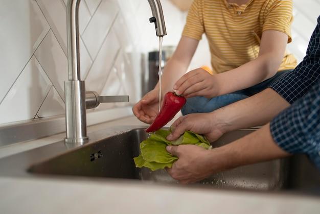 Feche as mãos lavando vegetais