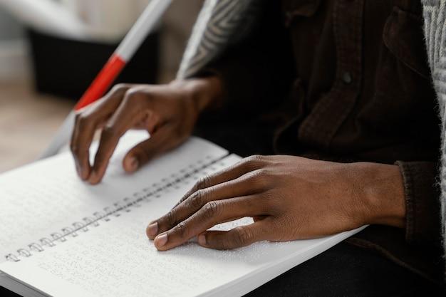 Feche as mãos lendo um caderno de braille