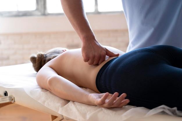Feche as mãos massageando a parte inferior das costas