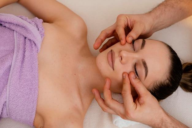 Feche as mãos massageando as bochechas