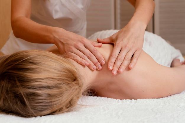 Feche as mãos massageando as costas da mulher
