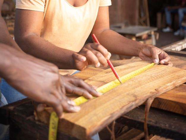 Feche as mãos medindo madeira