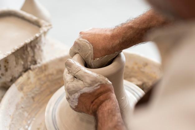 Feche as mãos modelando argila