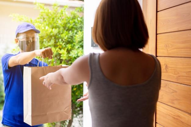 Feche as mãos mulher cliente recice saco de papel de entrega homem asiático enviar para ela em casa