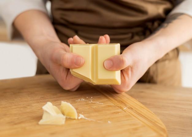 Feche as mãos quebrando o chocolate