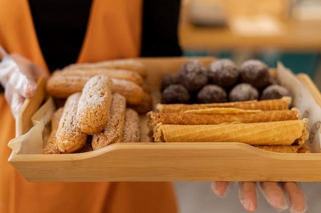 Feche as mãos segurando a bandeja com sobremesa