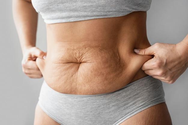 Feche as mãos segurando a gordura corporal