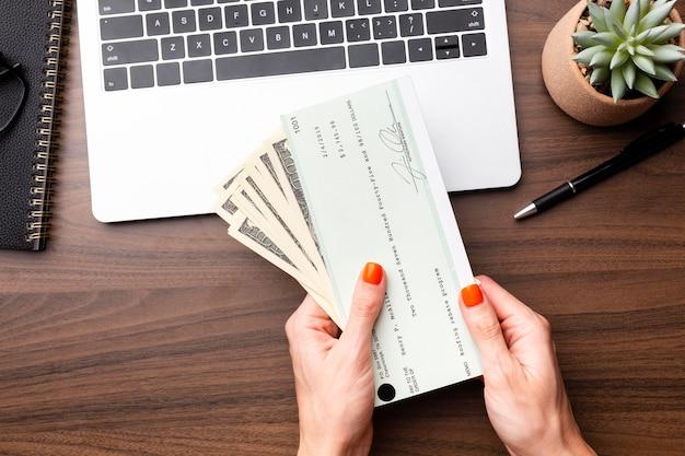 Feche as mãos segurando dinheiro e cheque