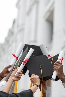 Feche as mãos segurando diplomas e bonés