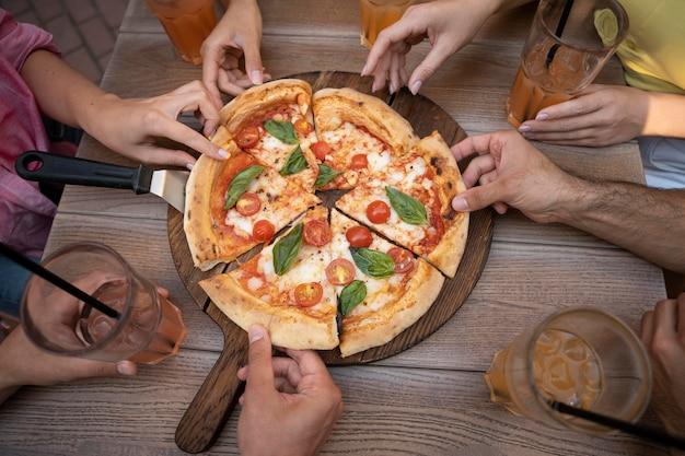 Feche as mãos segurando fatias de pizza