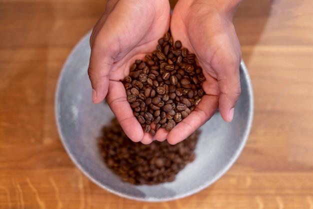 Feche as mãos segurando grãos de café