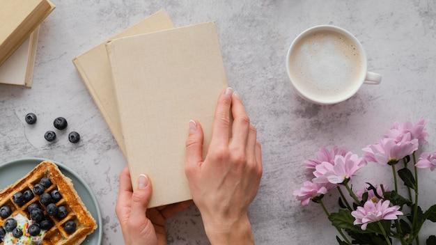 Feche as mãos segurando livros