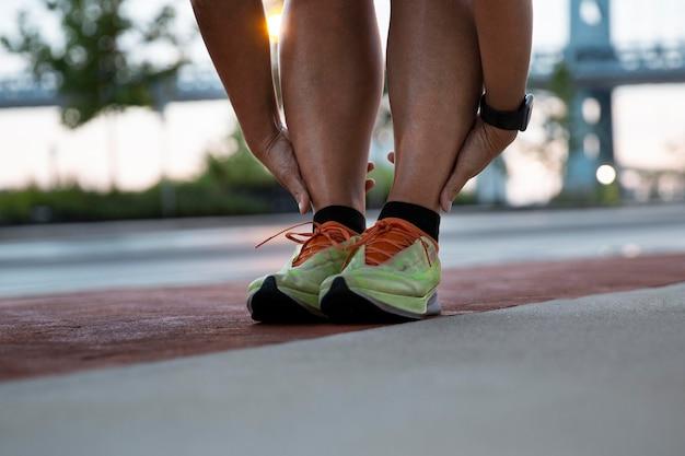 Feche as mãos segurando os tornozelos