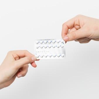 Feche as mãos segurando pílulas anticoncepcionais