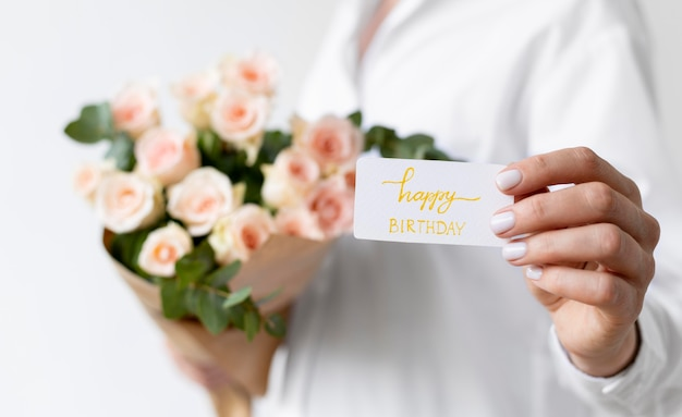 Feche as mãos segurando um bilhete e flores
