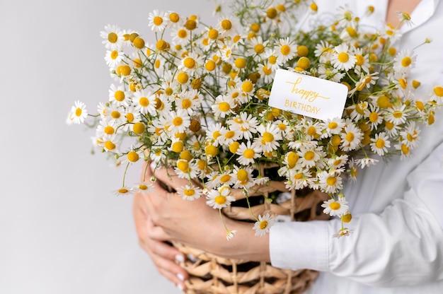 Feche as mãos segurando um buquê de flores