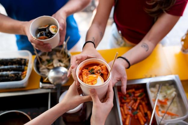 Feche as mãos segurando um copo com comida