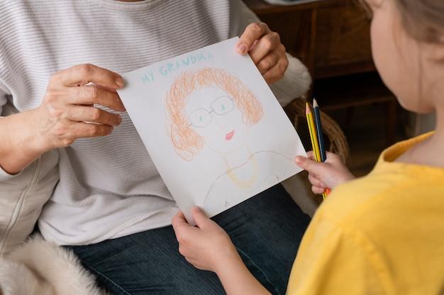 Feche as mãos segurando um desenho fofo