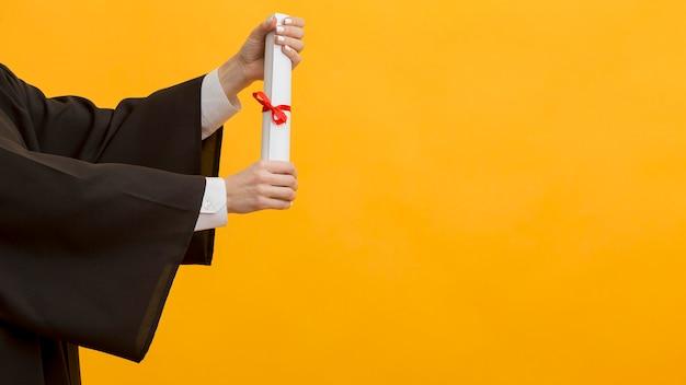 Feche as mãos segurando um diploma