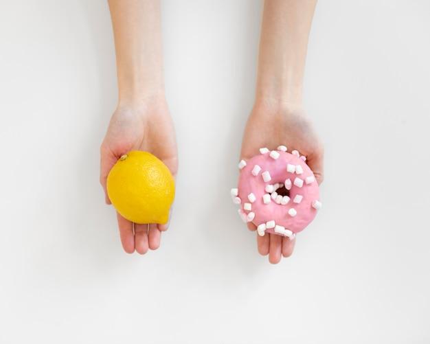 Feche as mãos segurando um limão e um donut