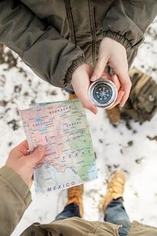 Feche as mãos segurando um mapa e uma bússola