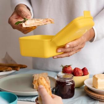 Feche as mãos segurando um sanduíche