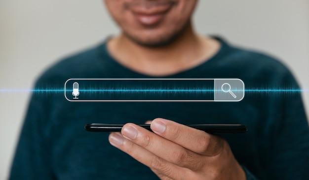Feche as mãos segurando um smartphone. homem que trabalha com smartphone e com a barra de pesquisa em branco.
