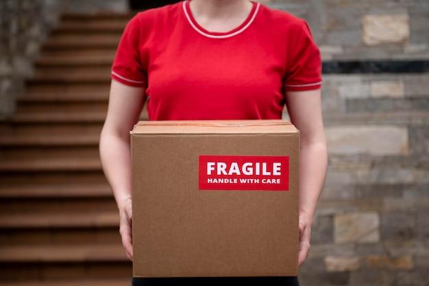 Feche as mãos segurando uma caixa frágil