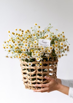 Feche as mãos segurando uma cesta com flores