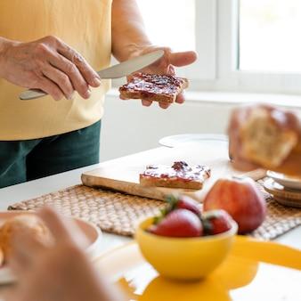 Feche as mãos segurando uma faca e um pão
