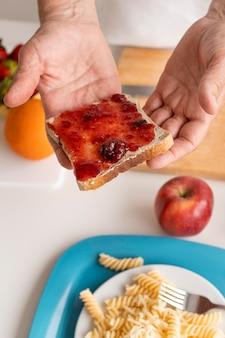 Feche as mãos segurando uma fatia de pão com geleia