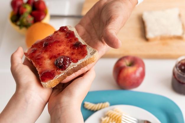 Feche as mãos segurando uma fatia de pão