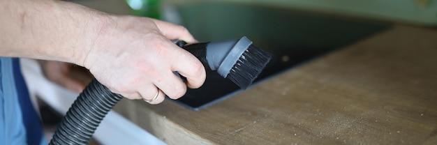 Feche as mãos segurando uma mangueira com escova de cozinha. serviço que requer profissionalismo do contratante. produtos de limpeza de eficácia na luta contra vírus. remoção de gordura de superfícies duras