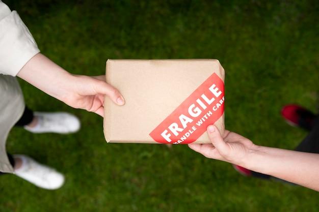Feche as mãos segurando uma mochila frágil