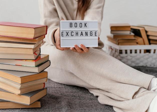 Feche as mãos segurando uma placa de troca de livro