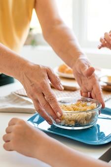 Feche as mãos segurando uma tigela com macarrão