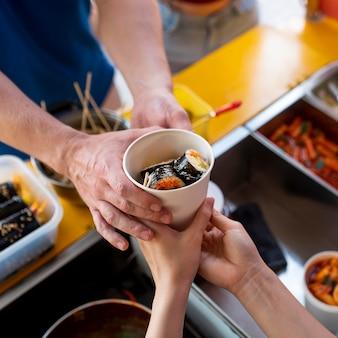 Feche as mãos segurando uma xícara com sushi