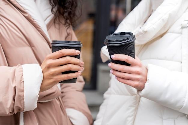 Feche as mãos segurando xícaras de café