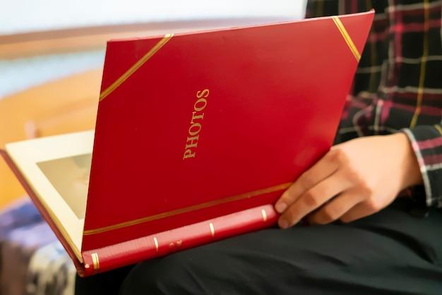 Feche as mãos segure e abra o álbum de fotos em família vermelho sentado em casa, passado conceito de memória f