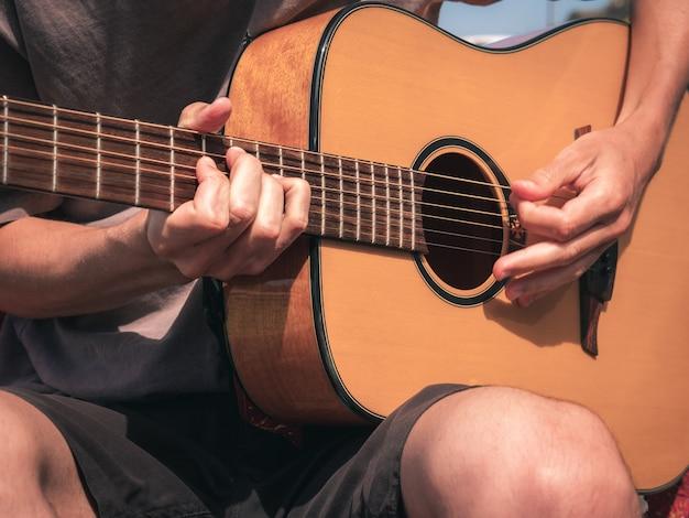 Feche as mãos sobre as cordas de uma guitarra canhoto com capo. vista frontal