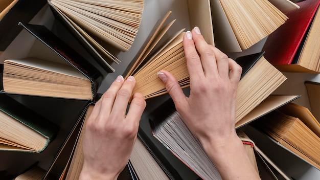 Feche as mãos tocando livros
