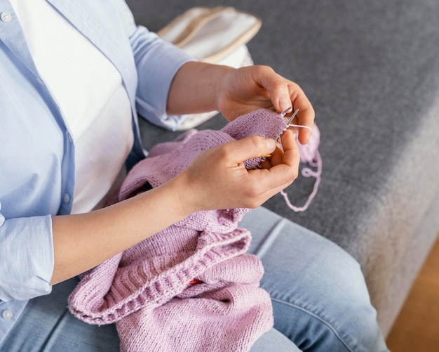 Feche as mãos tricotando dentro de casa