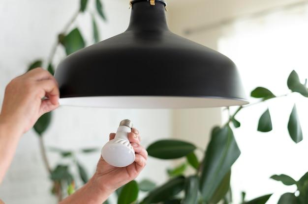 Feche as mãos trocando a lâmpada