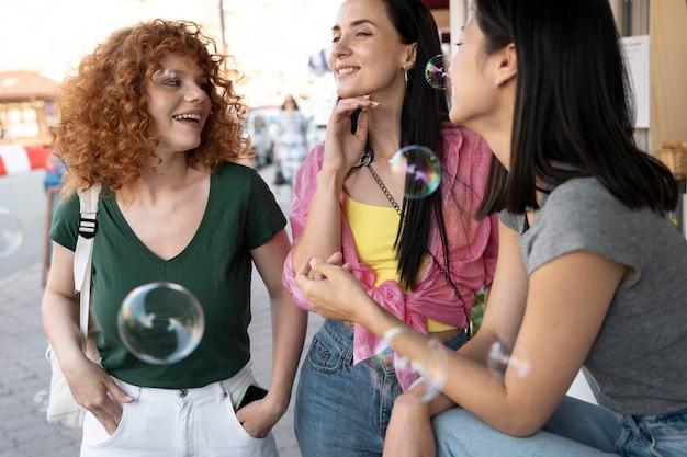 Feche as mulheres com bolhas de sabão