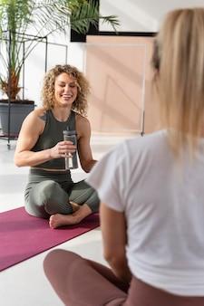 Feche as mulheres dentro de casa com tapete de ioga